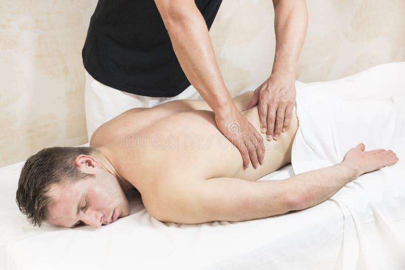 Homem novo na massagem dos tratamentos do bem-estar fotos de stock
