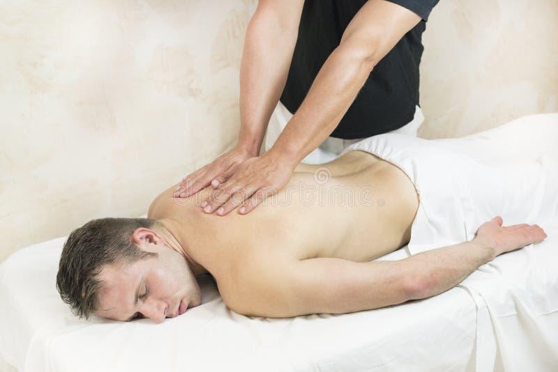 Homem novo na massagem dos tratamentos do bem-estar foto de stock