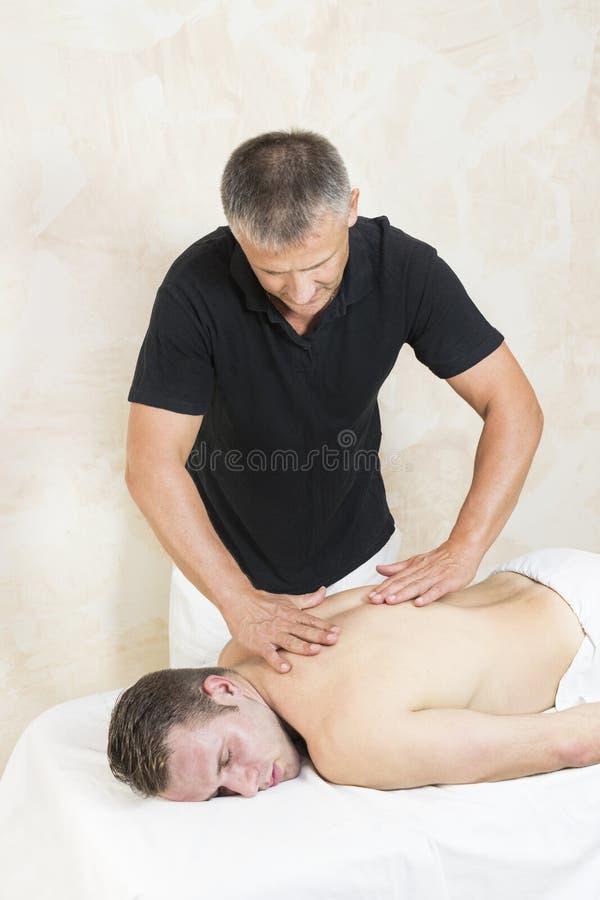 Homem novo na massagem dos tratamentos do bem-estar fotografia de stock royalty free