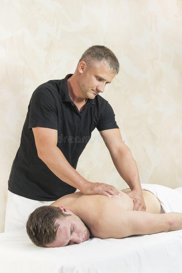 Homem novo na massagem dos tratamentos do bem-estar imagens de stock royalty free