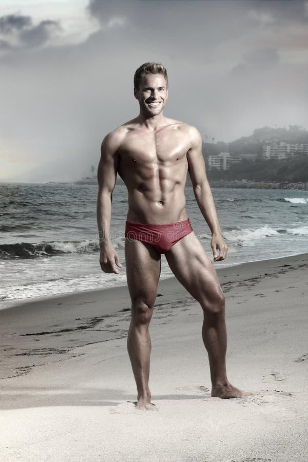Homem novo na praia imagem de stock royalty free