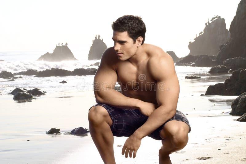 Homem novo na praia imagens de stock royalty free