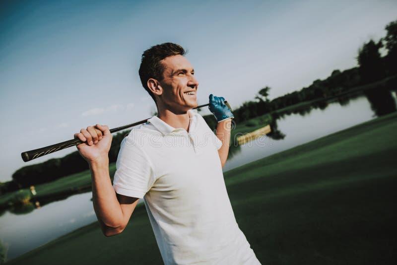 Homem novo na roupa branca que joga o golfe no campo imagens de stock royalty free