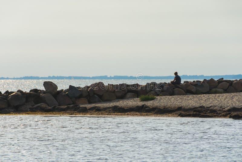 Homem novo na roupa dos esportes que senta-se em pedras no litoral e que olha a superfície e o por do sol do mar fotografia de stock royalty free
