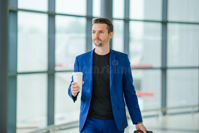 Homem novo no aeroporto Indivíduo ocasional com bagagem no aeroporto internacional foto de stock royalty free