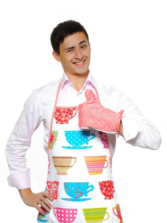 Homem novo no avental que prepara-se para cozinhar foto de stock royalty free