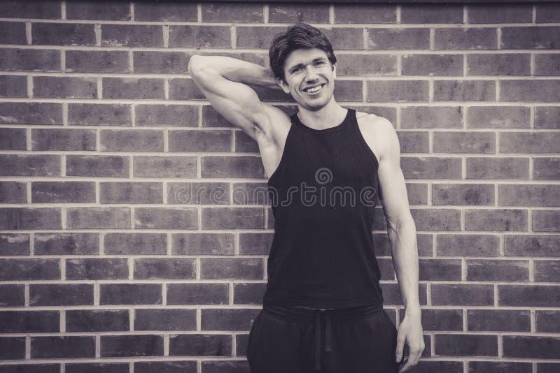 Homem novo no bíceps de dobramento superior da veste imagens de stock royalty free