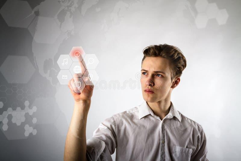 Homem novo no branco que empurra o botão Conceito inovativo da tecnologia imagens de stock royalty free