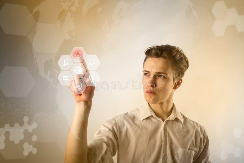 Homem novo no branco que empurra o botão Conceito inovativo da tecnologia fotografia de stock