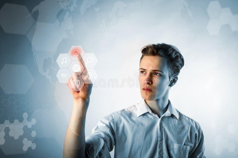 Homem novo no branco que empurra o botão Conceito inovativo da tecnologia imagem de stock royalty free