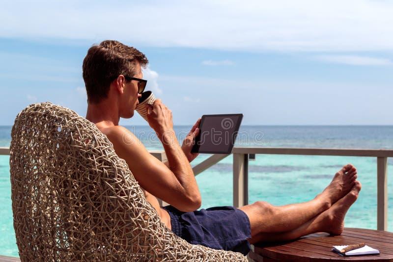 Homem novo no café bebendo do roupa de banho e trabalho em uma tabuleta em um destino tropical fotos de stock royalty free
