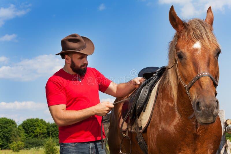 Homem novo no chapéu de vaqueiro que sela seu cavalo marrom fotografia de stock royalty free