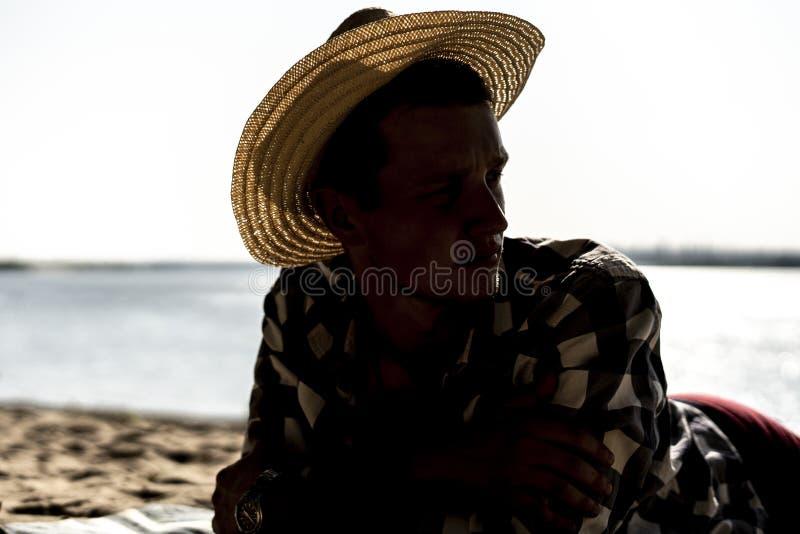 Homem novo no chapéu do verão que encontra-se na praia do mar um fim acima dos retratos imagens de stock