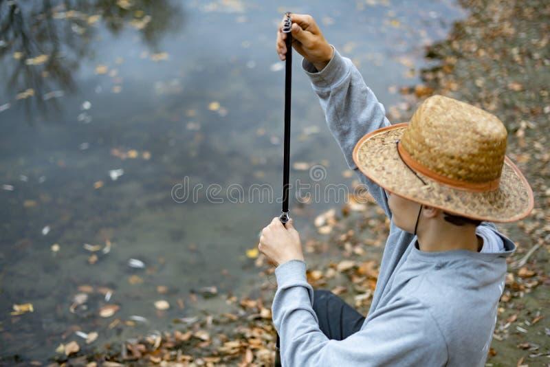 Homem novo no chapéu que senta-se perto do lago e para instalar para estabelecer e ajustar a vara de pesca f imagem de stock royalty free