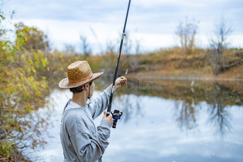 Homem novo no chapéu que senta-se perto do lago e para instalar para estabelecer e ajustar a vara de pesca f foto de stock