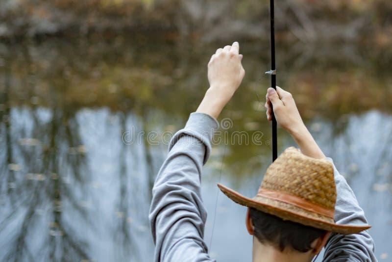 Homem novo no chapéu que senta-se perto do lago e para instalar para estabelecer e ajustar a vara de pesca f fotos de stock