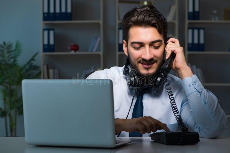 Homem novo no conceito do centro de atendimento que trabalha horas extras atrasadas no escritório fotografia de stock