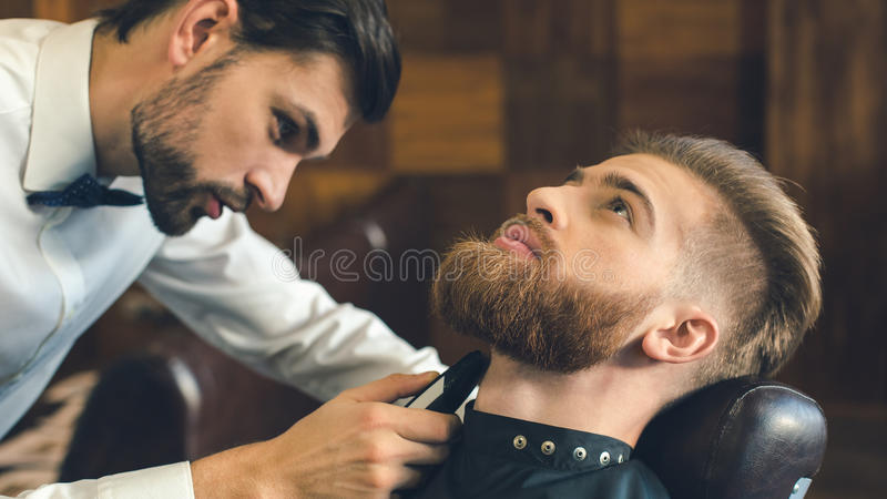 Homem novo no conceito do serviço dos cuidados capilares do barbeiro fotografia de stock