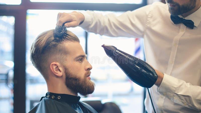 Homem novo no conceito do serviço dos cuidados capilares do barbeiro imagem de stock royalty free