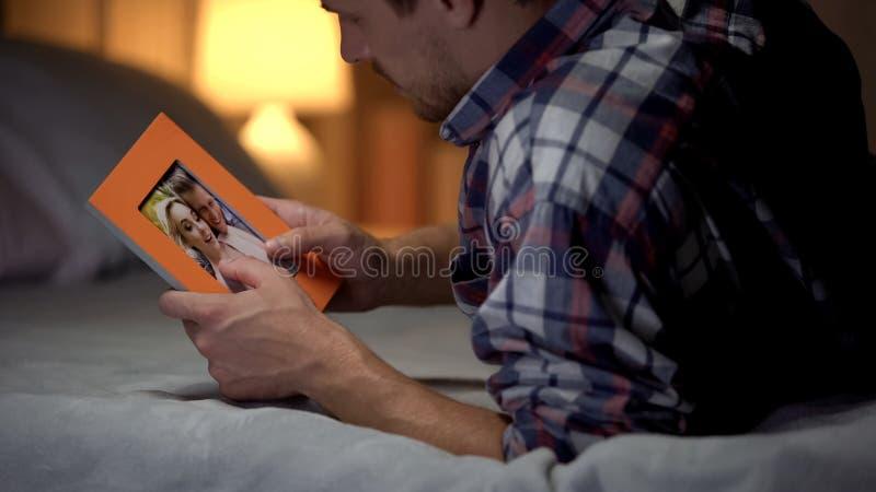 Homem novo no desespero que encontra-se na cama que olha a foto com amiga, tristeza imagem de stock