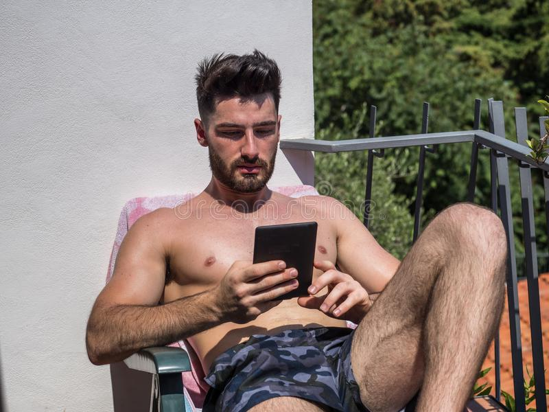 Homem novo no ebook da leitura da cadeira de sala de estar foto de stock