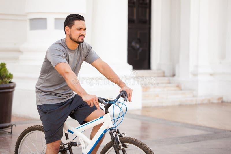 Homem novo no equipamento desportivo que monta uma bicicleta imagem de stock royalty free