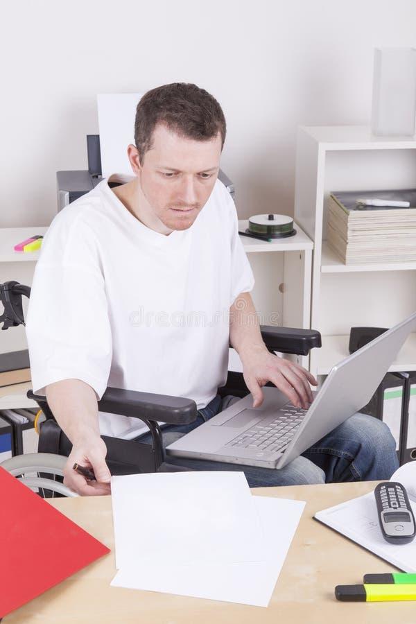 Homem novo no escritório da cadeira de rodas em casa fotografia de stock royalty free