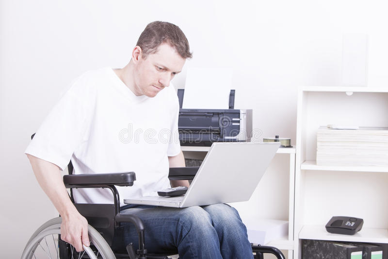 Homem novo no escritório da cadeira de rodas em casa fotos de stock royalty free