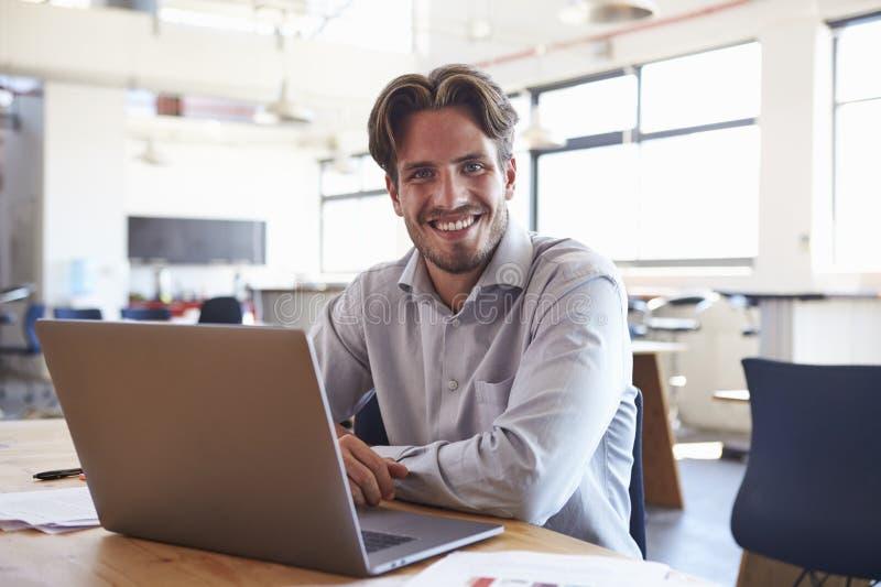 Homem novo no escritório usando o laptop que sorri à câmera fotos de stock