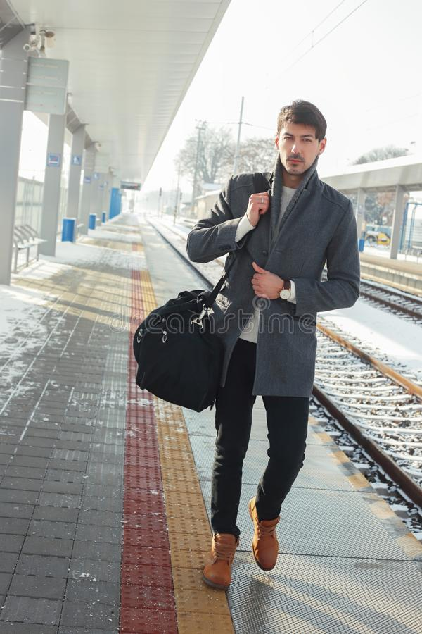 Homem novo no estação de caminhos-de-ferro foto de stock