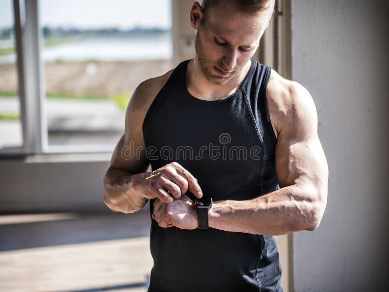 Homem novo no gym que verifica o relógio dos esportes fotos de stock royalty free