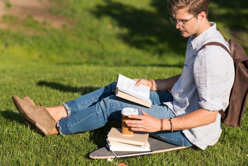 Homem novo no livro de leitura dos espetáculos e no café bebendo ao sentar-se no skate no parque fotografia de stock royalty free