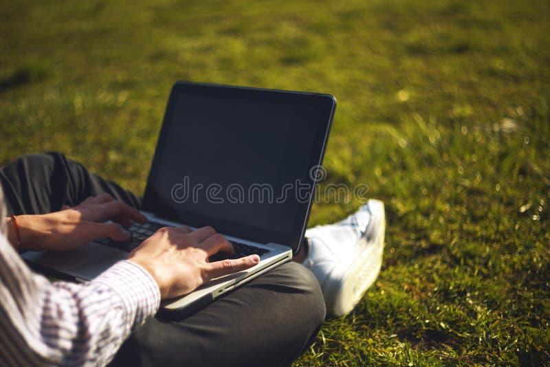 Homem novo no parque que senta-se na grama com um portátil Equipe o laptop de utilização e de datilografia na grama do verão fotografia de stock