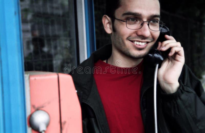 Homem novo no payphone imagens de stock