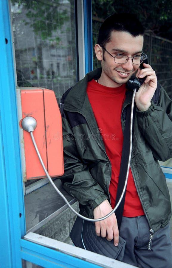 Homem novo no payphone imagem de stock