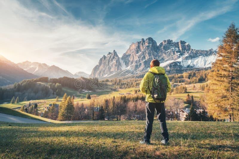 Homem novo no revestimento amarelo com a trouxa no vale da montanha fotografia de stock royalty free