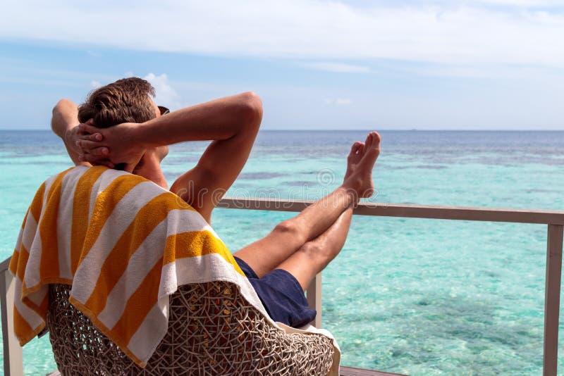 Homem novo no roupa de banho que relaxa em um terraço e que aprecia a liberdade em um destino tropical imagens de stock