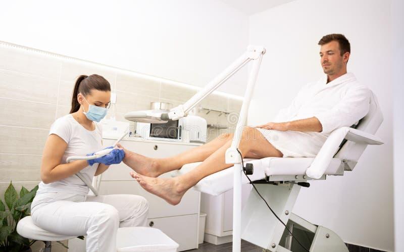 Homem novo no salão de beleza dos termas no tratamento do pedicure imagem de stock royalty free