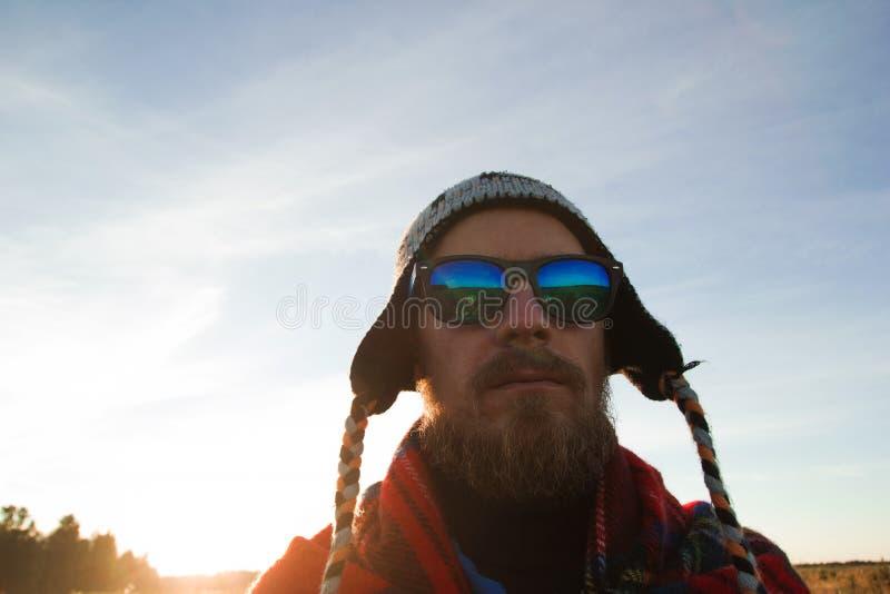 Homem novo no tampão, nos óculos de sol e na cobertura feitos malha no fundo de um campo e de um céu azul fotos de stock royalty free