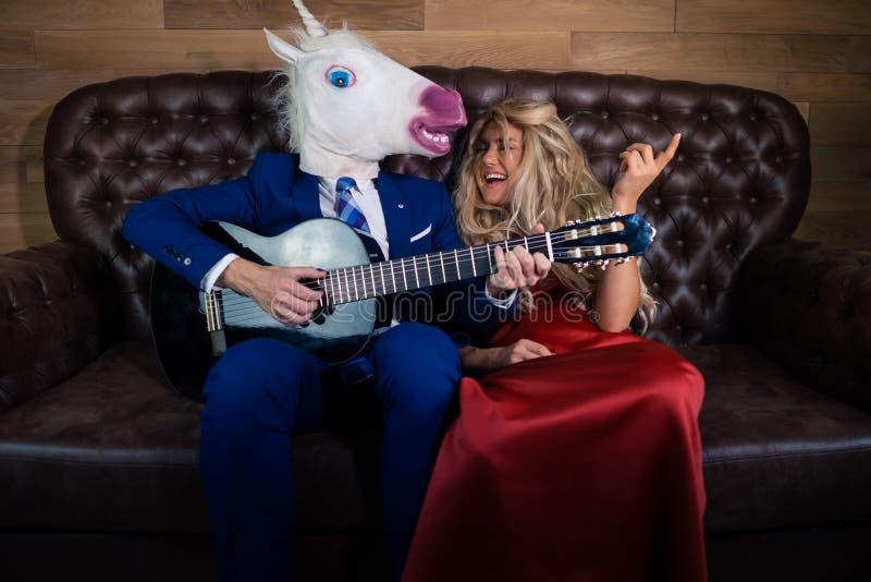 Homem novo no terno elegante e na máscara cômico que jogam a música na guitarra foto de stock