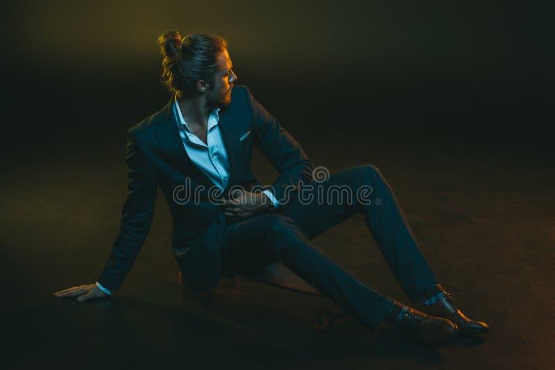 Homem novo no terno elegante que senta-se no skate fotografia de stock