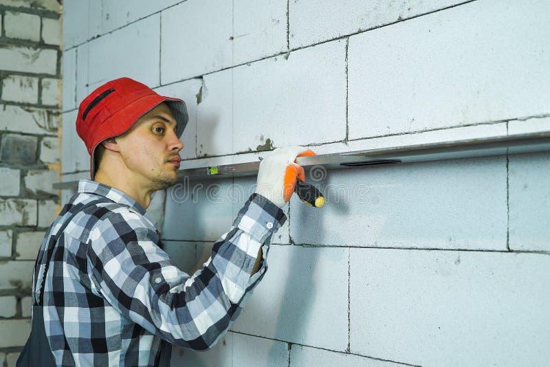 Homem novo no trabalho para vestir a verificação da retidão da parede do bloco com o nível de bolha fotografia de stock royalty free