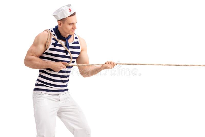 Homem novo no uniforme do marinheiro que puxa uma corda foto de stock royalty free