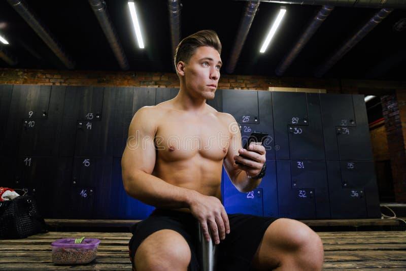 Homem novo no vestuario do gym Indivíduo considerável no estúdio da aptidão que faz seu próprio pessoal antes de treinar imagens de stock