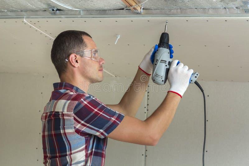 Homem novo nos óculos de proteção que fixam o teto suspendido do drywall para metal f foto de stock