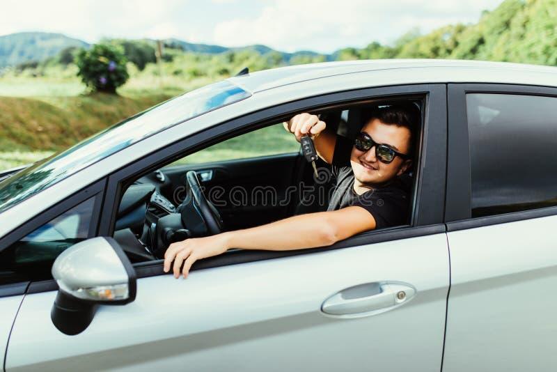 Homem novo nos óculos de sol que sentam-se em chaves do carro da terra arrendada do carro fora fotografia de stock royalty free