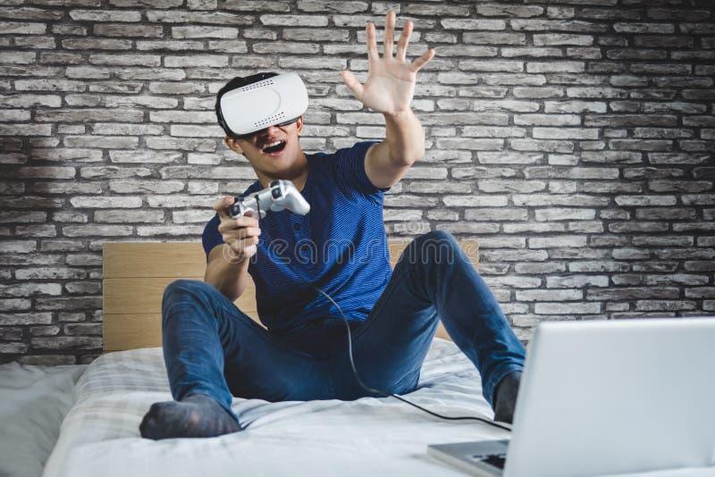 Homem novo nos auriculares da realidade virtual ou nos vidros 3d que jogam o vídeo foto de stock