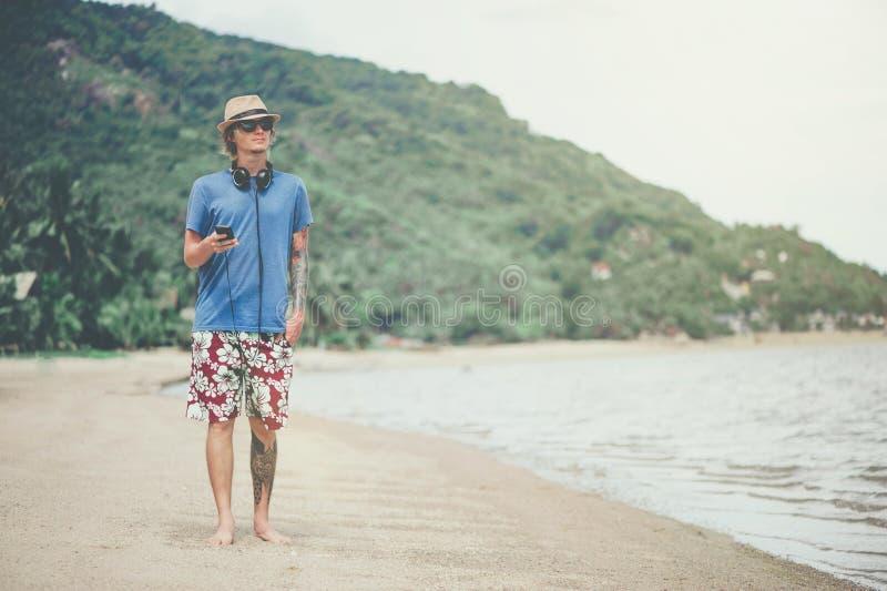 Homem novo nos fones de ouvido e nos óculos de sol na praia que escuta a música foto de stock
