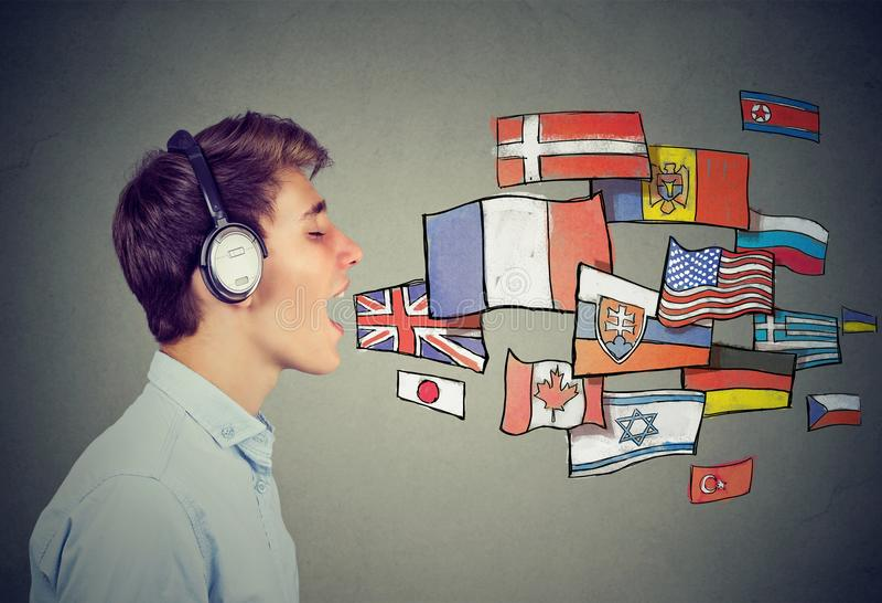 Homem novo nos fones de ouvido que aprende línguas diferentes fotos de stock royalty free