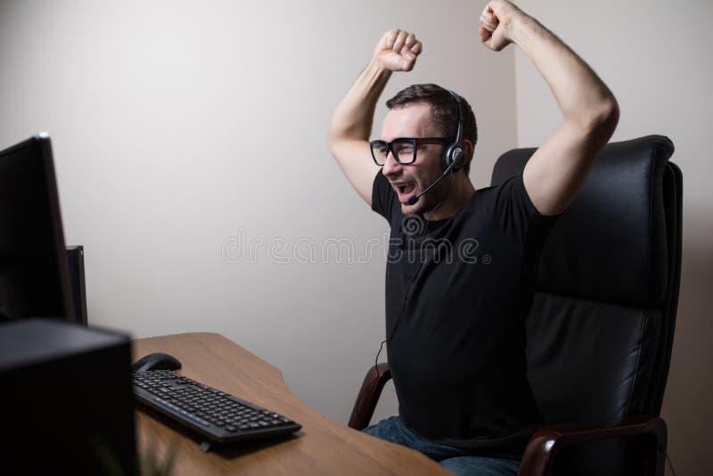 Homem novo nos monóculos com jogo de jogo e de vencimento dos auriculares de computador imagem de stock royalty free